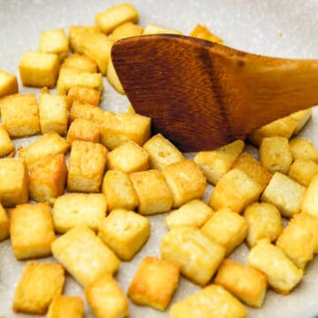 Tofu cubes frying and being stirred with a wooden spatula.