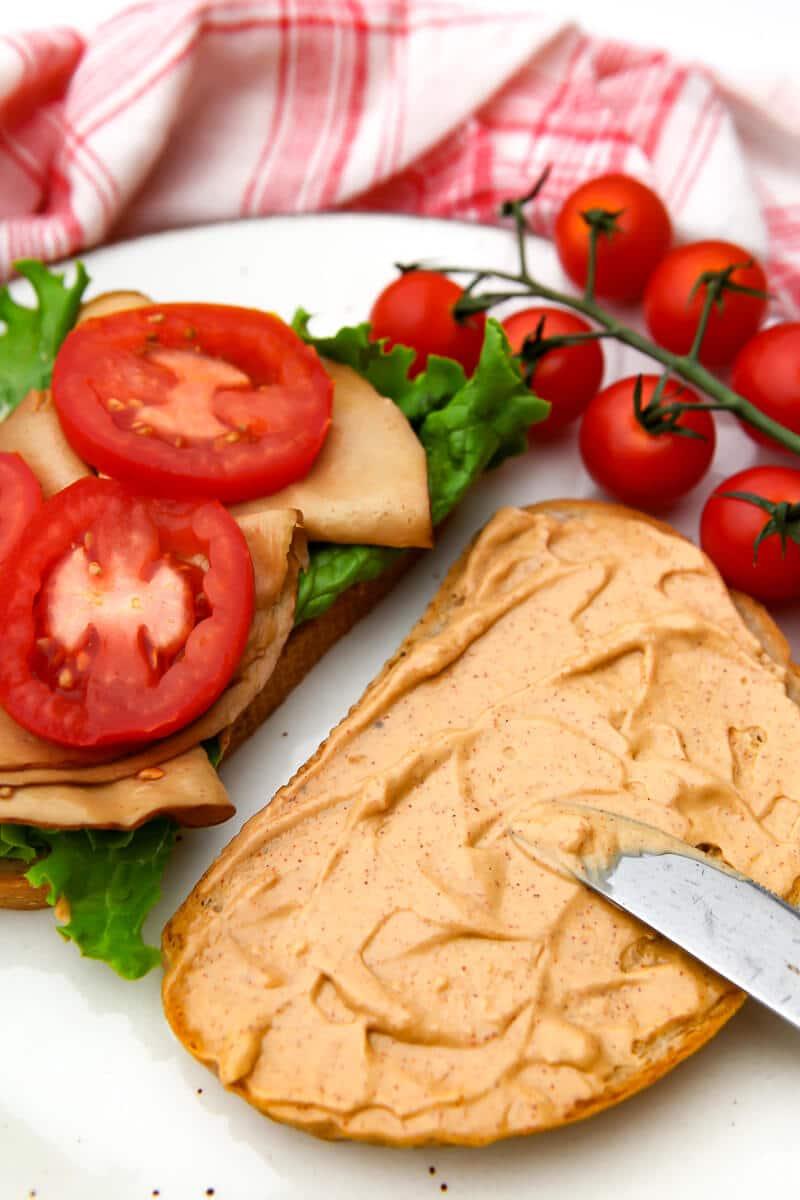 Someone spreading chipotle mayo on a vegan turkey sandwich.