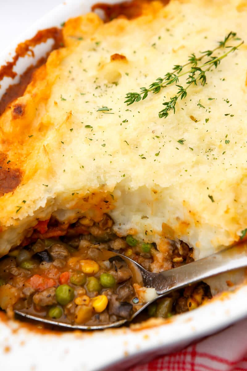A vegan cottage pie made with beyond beef crumbles with a scoop taken out of it.