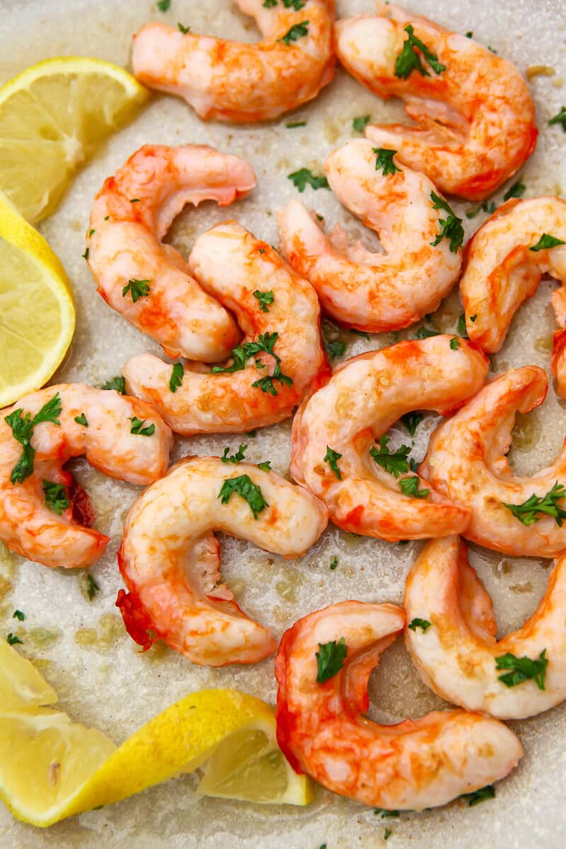 Vegan shrimp sauted in a pan with butter and garlic and sprinkled with fresh parsley and lemon wedges.